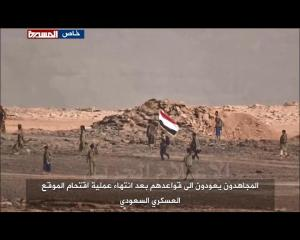 Yemeni soldiers hold Yemeni flag from Saudi military outpost in Asseer