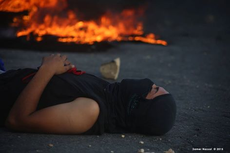 Palestinian guy resting near burning tires after a day of throwing stones on israeli occupational forces - unknown photographer