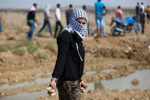 Palestinian girl holding stones in defense of her village against israeli occupation - unknown photographer