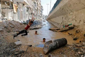 Kids swimming in a crater caused by bombing in Aleppo