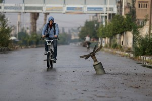 Young man riding by a bomb in Douma, Damascus