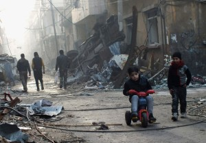 Syrian kid plays on tricycle in a besieged neighborhood by FSA in Homs