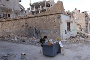 Syrian kid selling merchandises on a table in Der el Zour