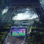 French fans watch final EURO 2016 game on big screen under Eiffel tower while others protest near by